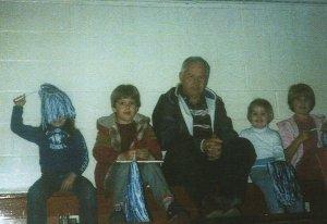 Sitting on the top row of Woodbridge Elementary School bleachers. I have no idea what we were watching. I am the one underneath the pom-pom. (Christy, Derek, Pop-Pop, Devon, Danna)